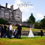 Bride playing golf to 18th green on her wedding day at Bovey Castle in Devon with hotel in the background