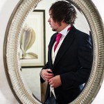 Reflection in mirror of Best man getting ready at Bovey Castle wedding in Devon.