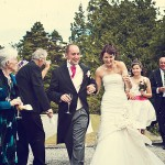 Bovey castle wedding photography of bride and groom walking through confetti shower hand in hand