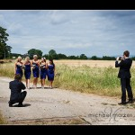 Guests photographing bridesmaids in fields at Somerset wedding