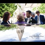 Somerset wedding photography of groom and church spire reflected in the wedding car roof.