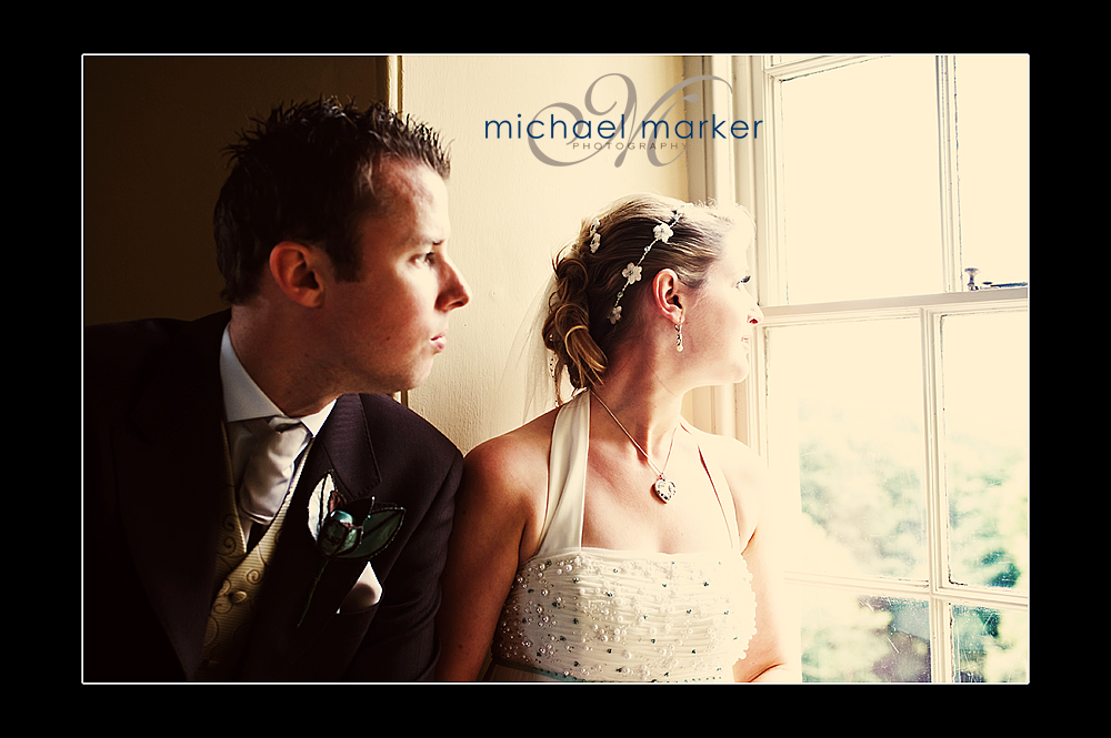 Bride and groom looking out of the staircase window at Haldon Belvedere wedding near Exeter