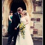 Bride and groom kiss outside church doorway at Plymouth wedding