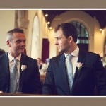 groom and bestman looking at each other nervously before wedding ceremony in Devon church