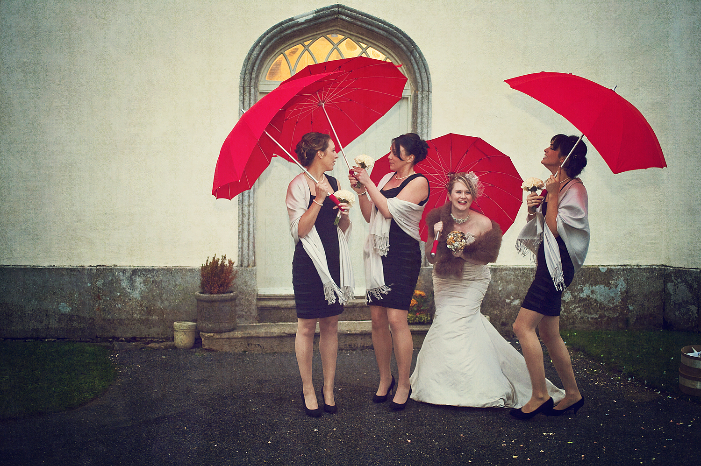 Bridesmaids with red umbrellas outside Haldon Belvedere in Devon