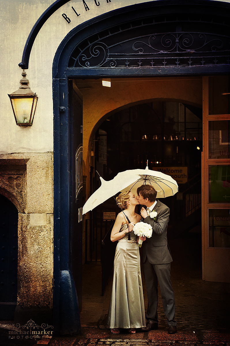 Wedding kiss outside Plymouth Gin Distillery