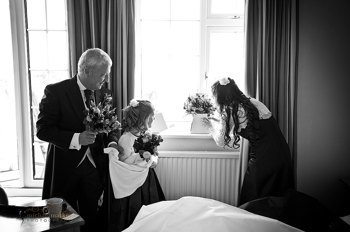 Father of the bride and bridesmaids drying flowers before the wedding