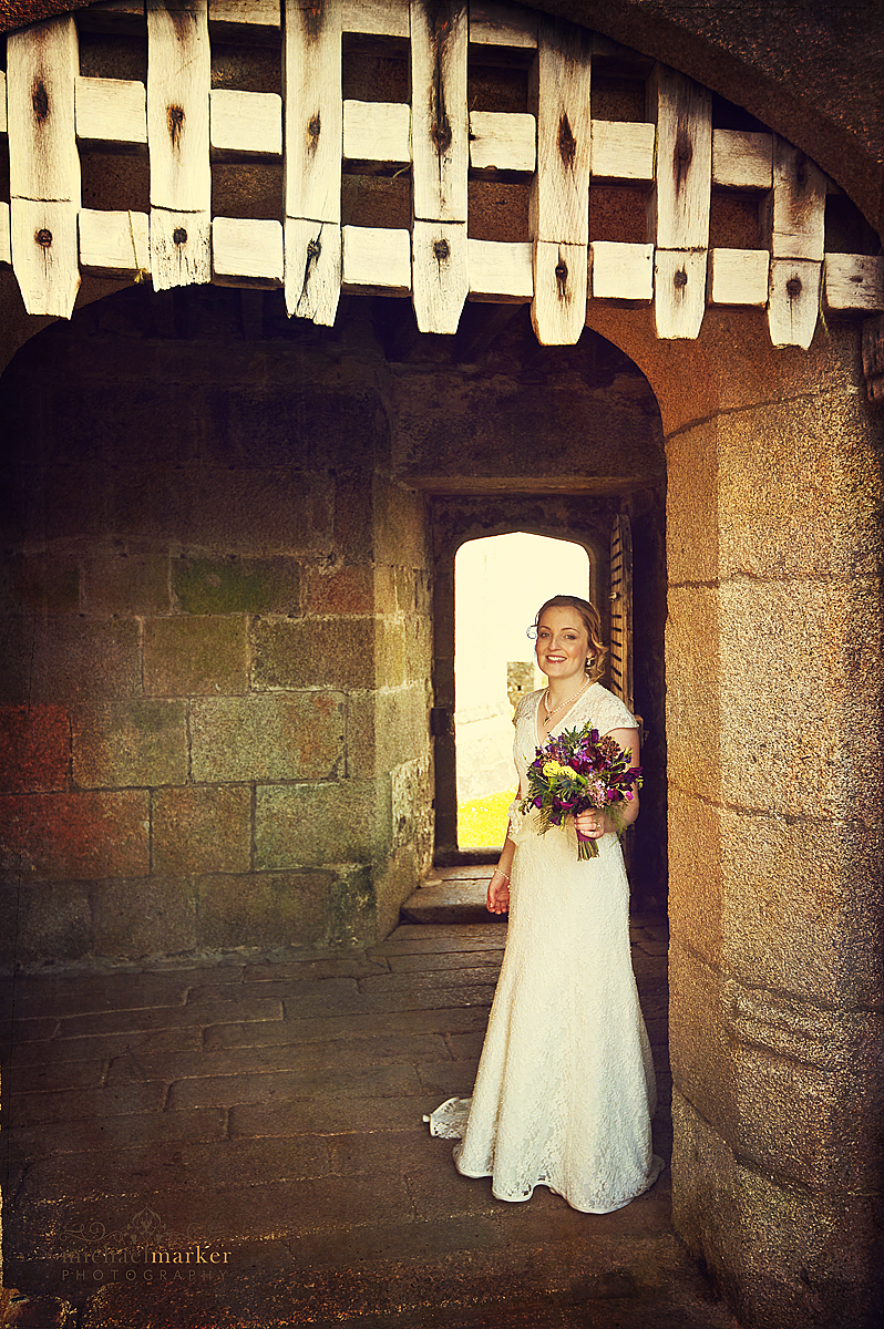 Bride outside Pendennis Castle with flowers for wedding in Falmouth
