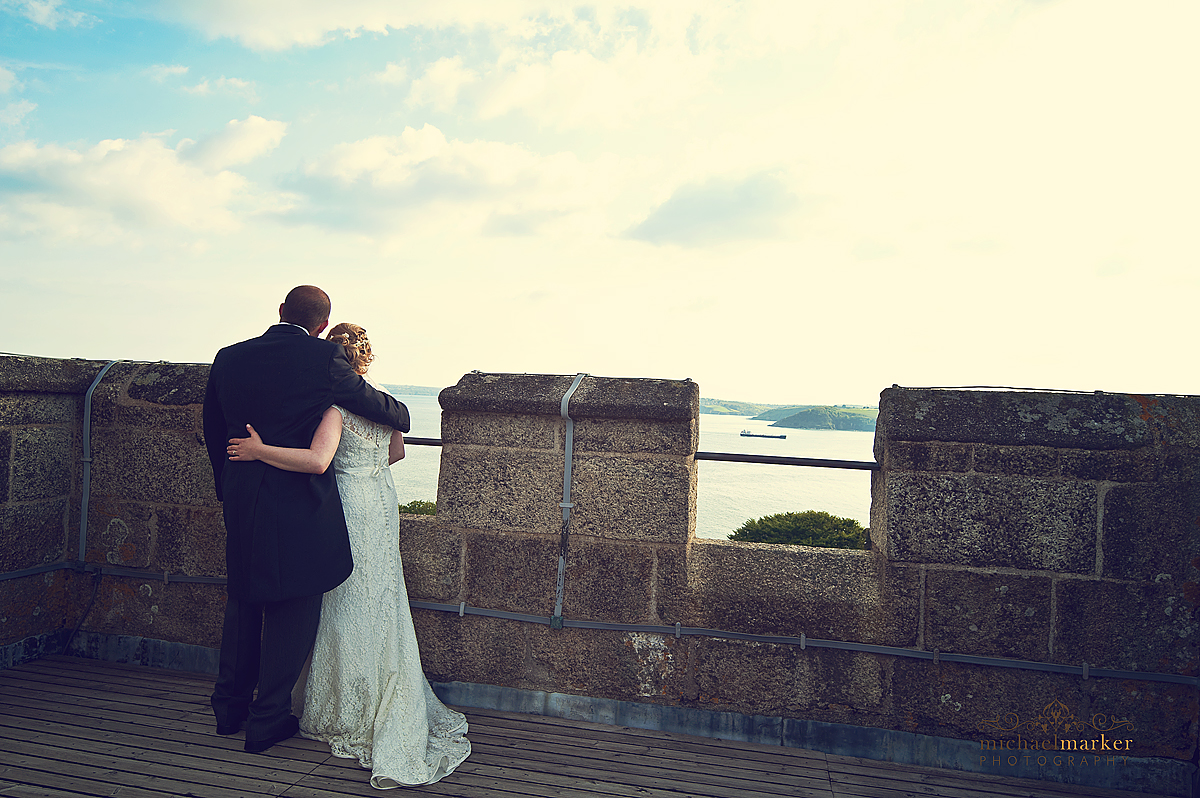 Couple at Falmouth wedding looking out from rooftop of Pendennis Castle.