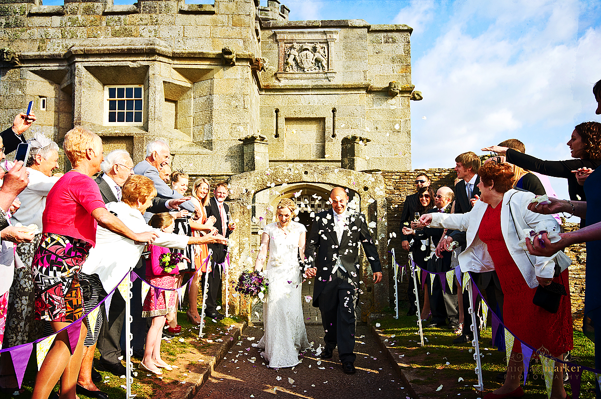 Confetti being thrown at couple as they leave Pendennis Castle entrance at Falmouth wedding