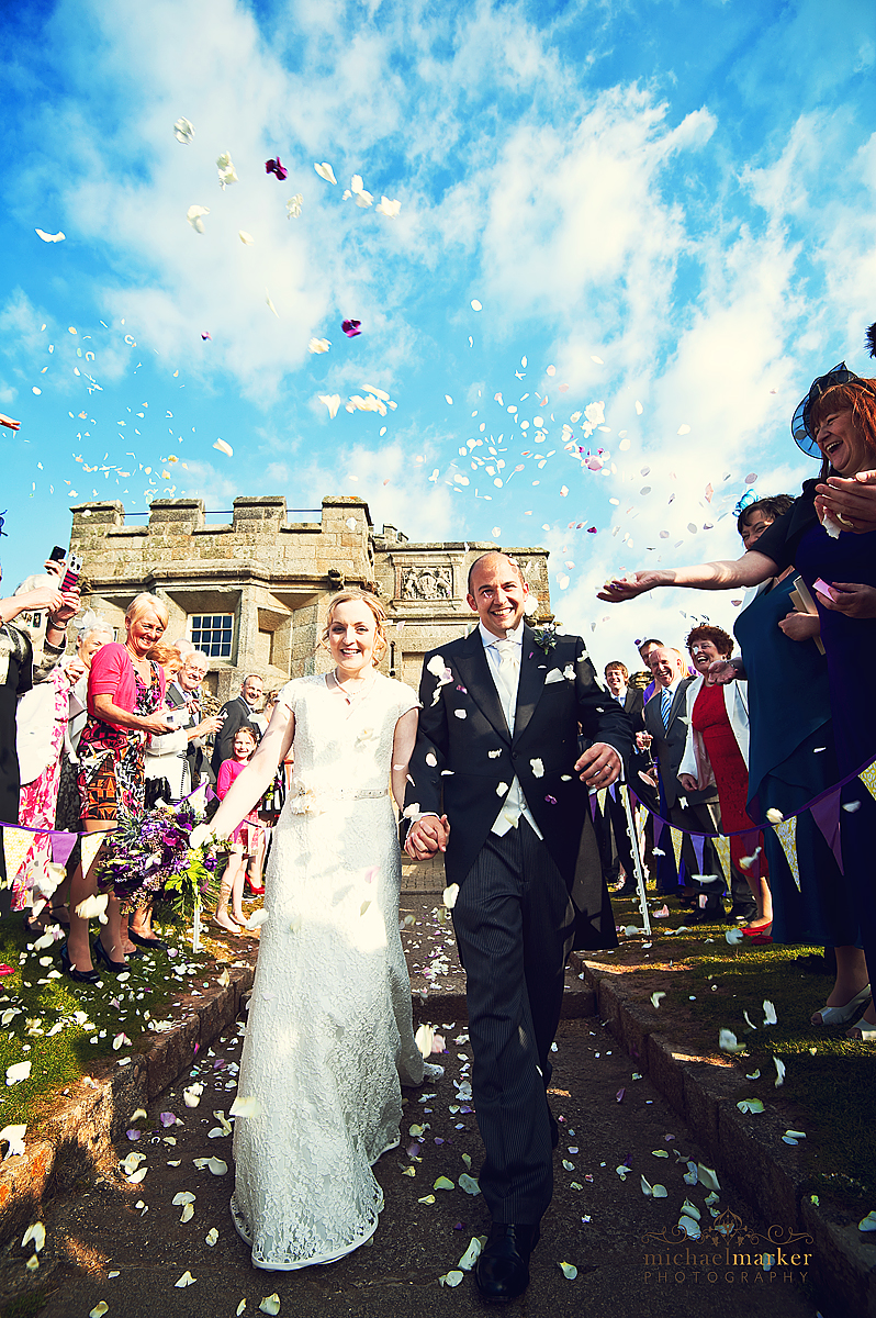 Pendennis Castle weddign - bride and groom walking through confetti