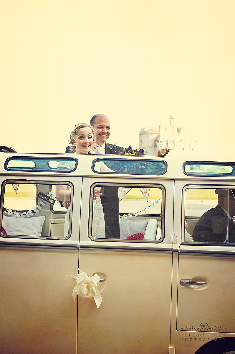 Cornwall wedding in Falmouth with bride and groom looking out of the roof of a vintage campervan parked in front of Pendennis Castle.