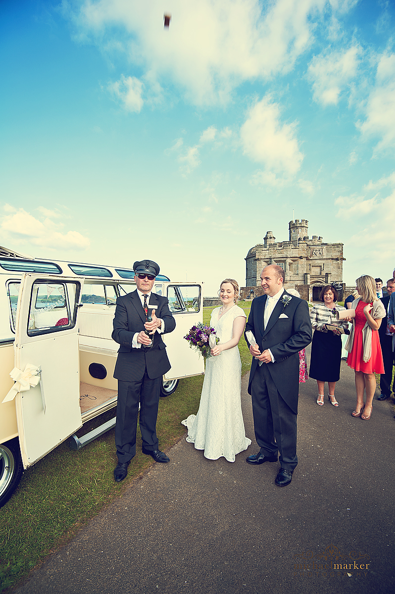 Bride and groom celebrating with champagne in front of Pendennis Castle in Cornwall