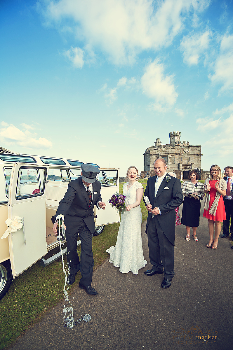 Falmouth wedding at Pendennis Castle opening the champagne for the bride and groom.