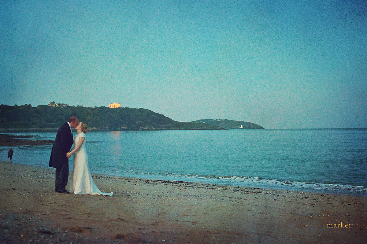 Bride and groom wedding photography on Falmouth beach on their wedding day with Pendennis Castle in the background.