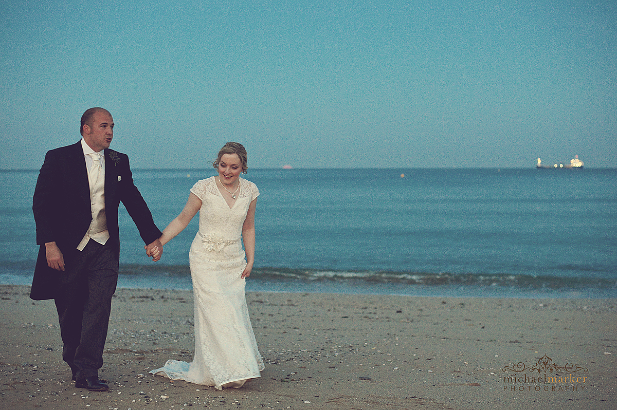 Bride and groom walking hand in hand along Falmouth beach in the early evening