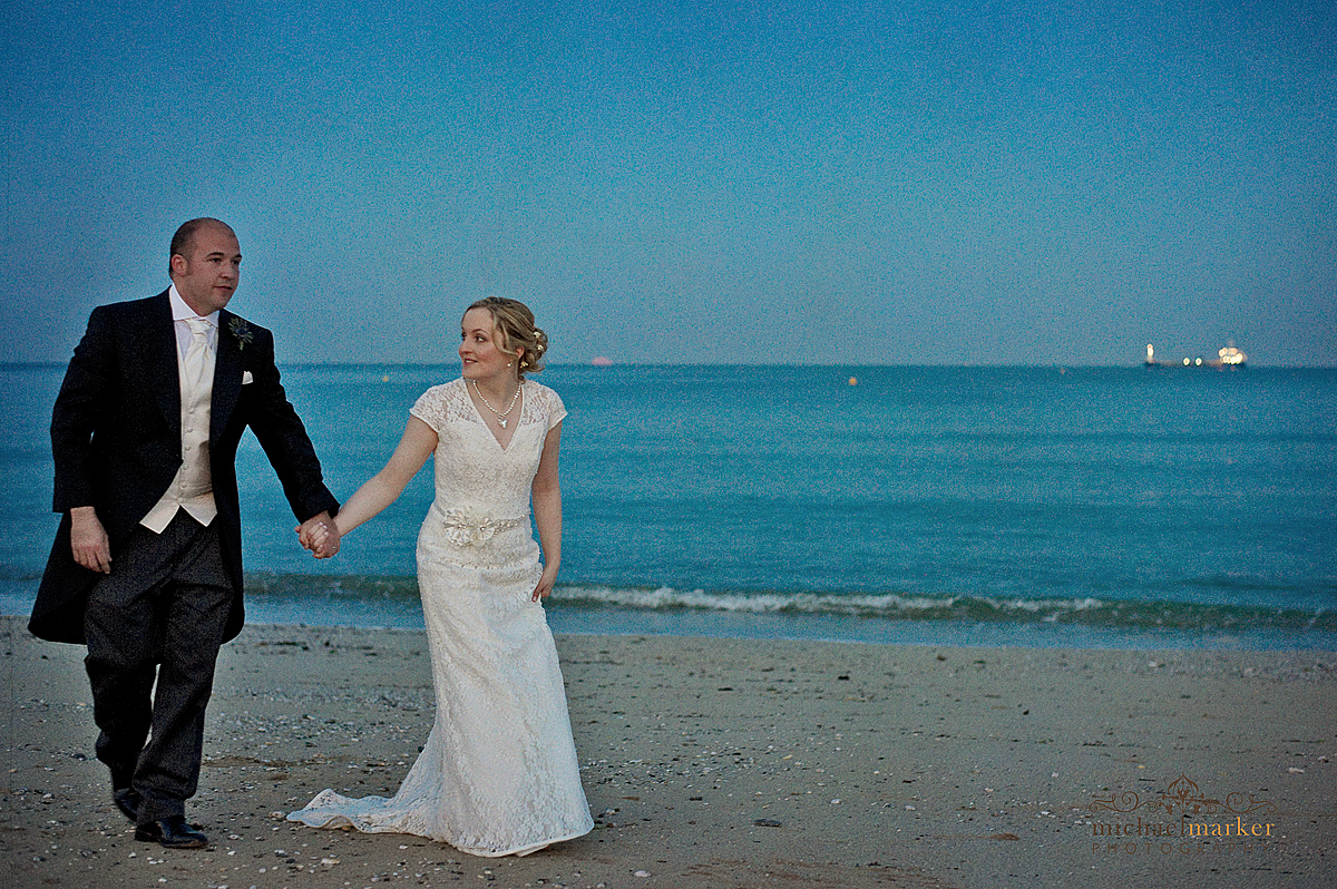 Cornish wedding couple walk on Falmouth beach at dusk.