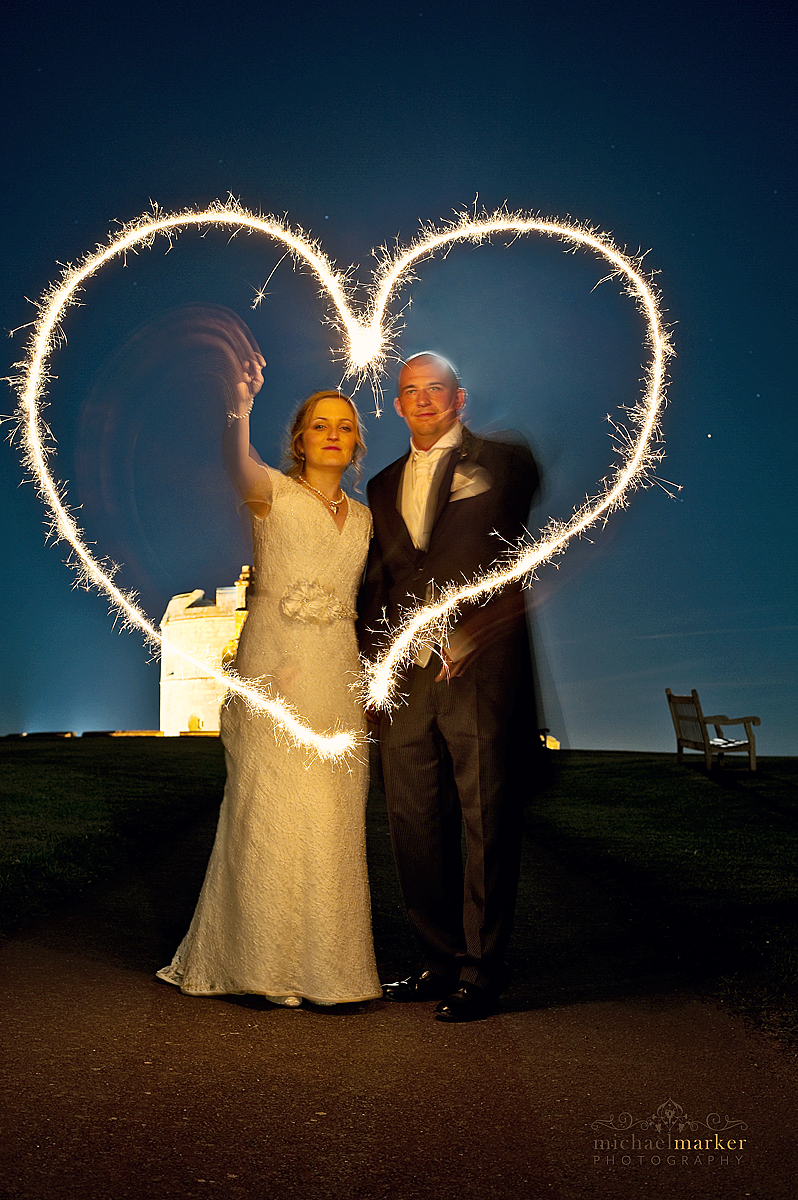 Falmouth wedding bride and groom creating sparkler heart shapes with Pendennis Castle in the background