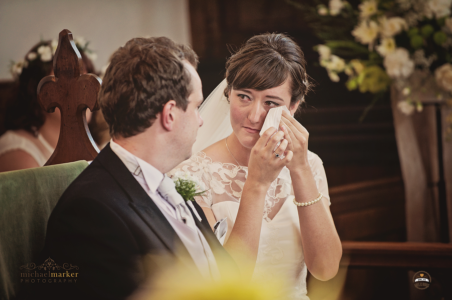 Bride wiping away tears during wedding ceremony