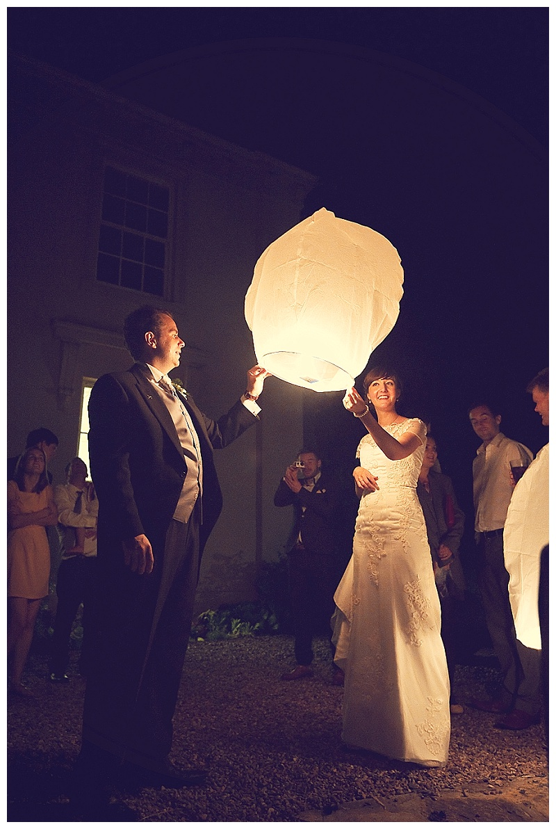 Bride and groom Lighting Chinese lanterns at North Devon wedding