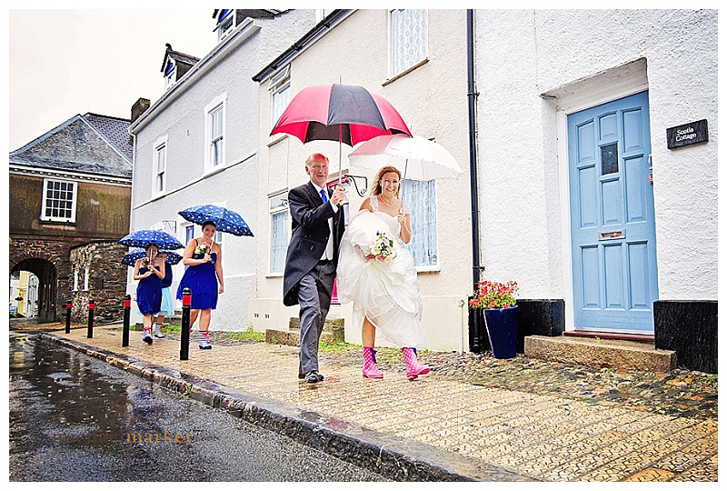 Bride and father and bridesmaids in Plympton St Maurice on the way to church in the rain