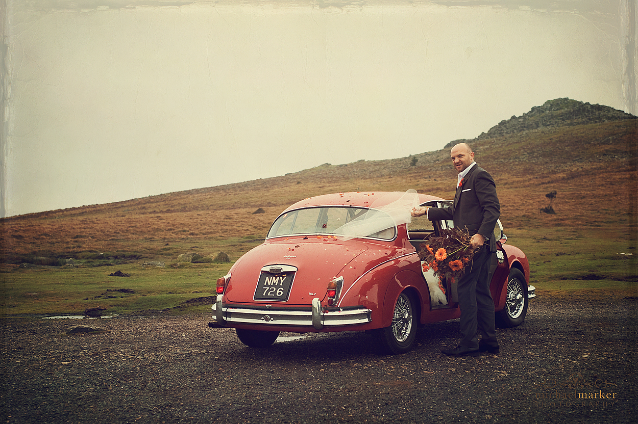 Groom and bride getting into vintage wedding car on Dartmoor in Devon