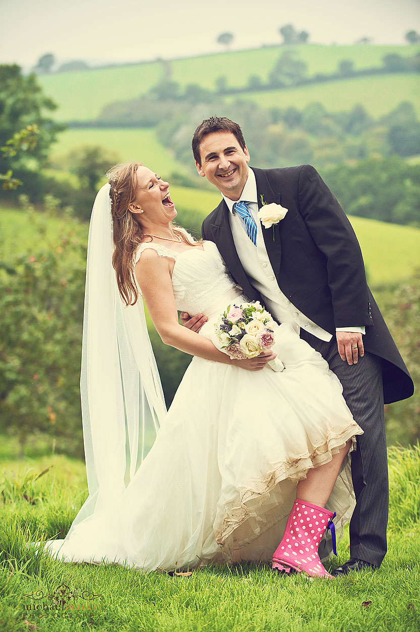 Wedding photography of Bride with pink wellies and groom at Cornish weddign at Lantallack House wedding venue