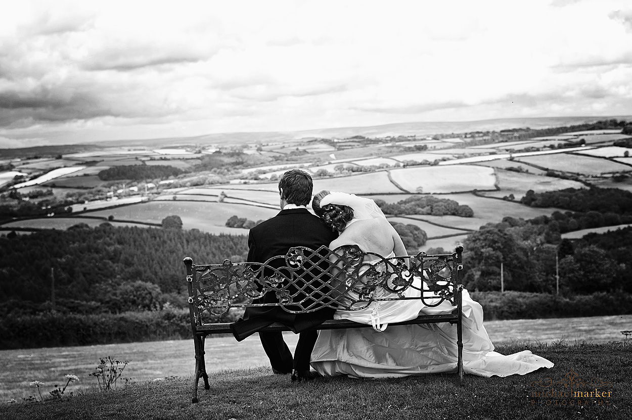 Black and white wedding photography of bride and groom on country bench