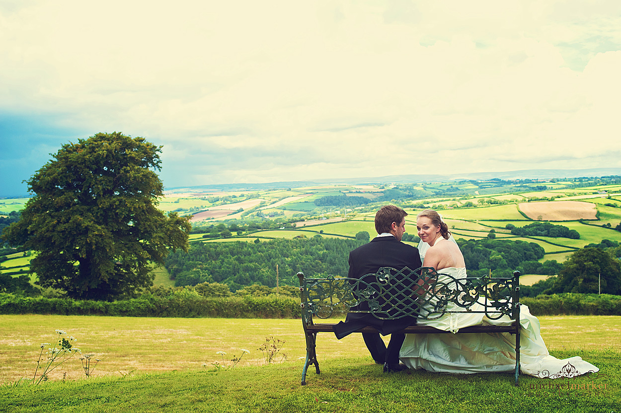 Wedding day couple on bench at Nortcote Manor in Devon