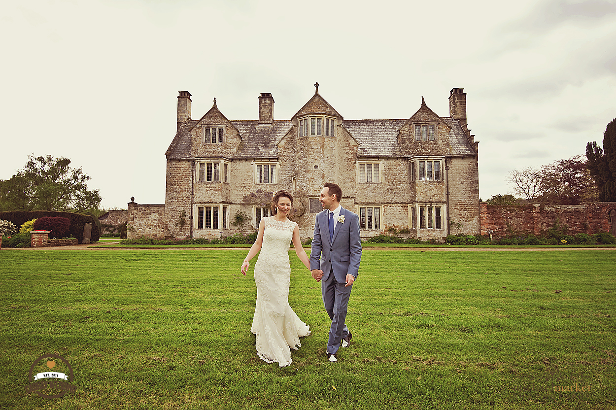 Married couple on wedding day in front of Cadhay Manor in Devon
