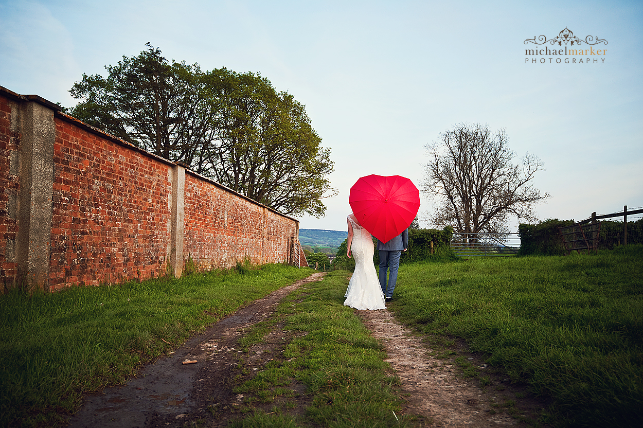 Wedding day couple at Cadhay Manor in Devon with Red umbrella