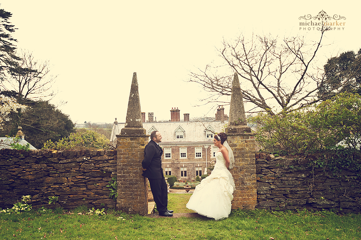 Bride and groom at Langdon Court in Devon overlooking the house from the gardens.