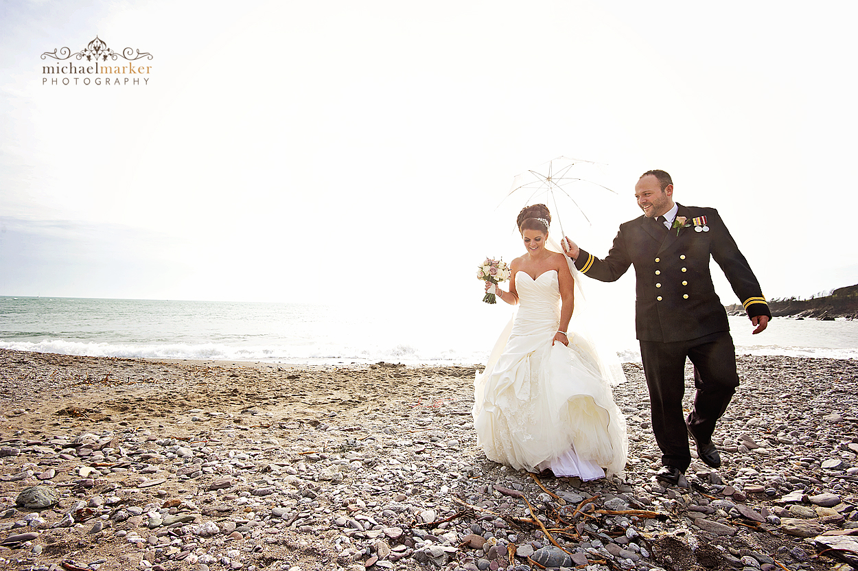 Wedding couple with umbrella on wembury beach in Devon