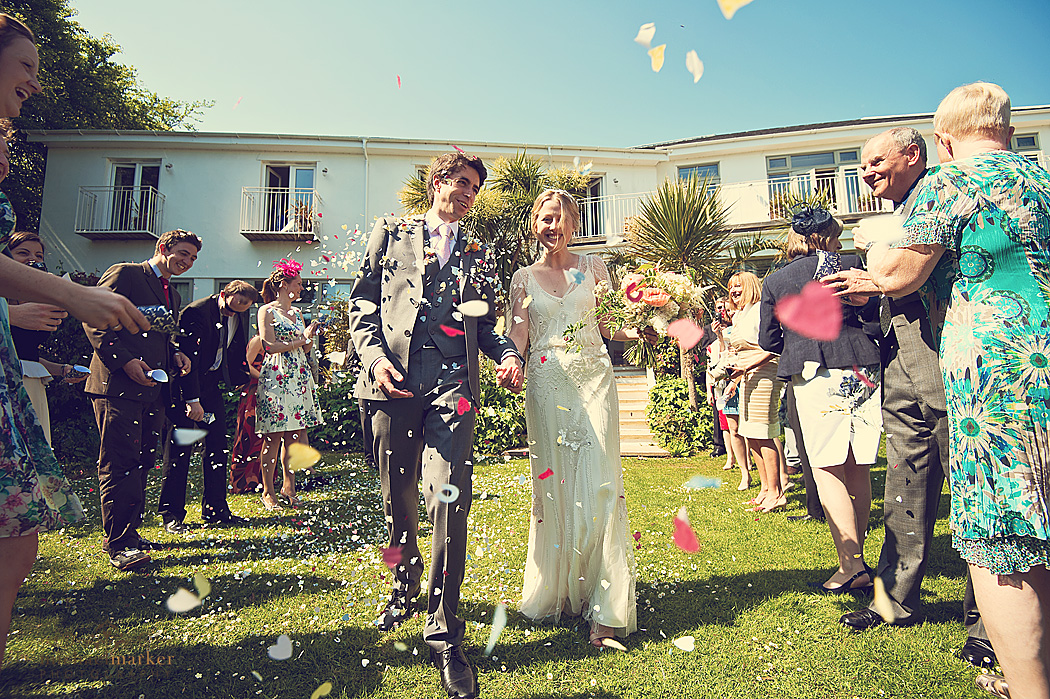 Confetti being thrown at bride and groom at Cornish wedding at The Rosevine