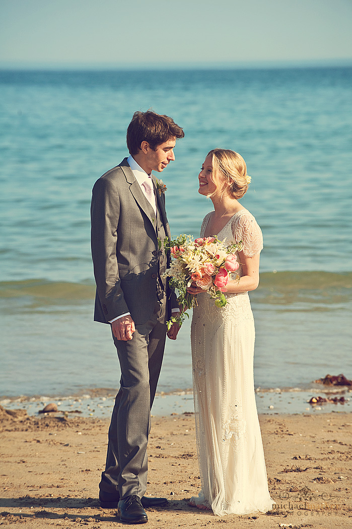 Bride and groom on Porthcurnick beach at Cornish beach wedding