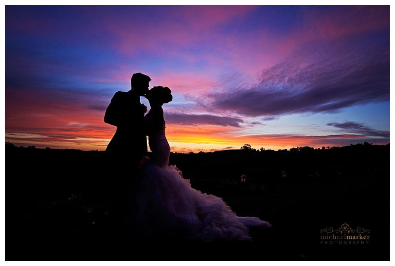 Bride and groom silhouette against colourful Cornish sunset