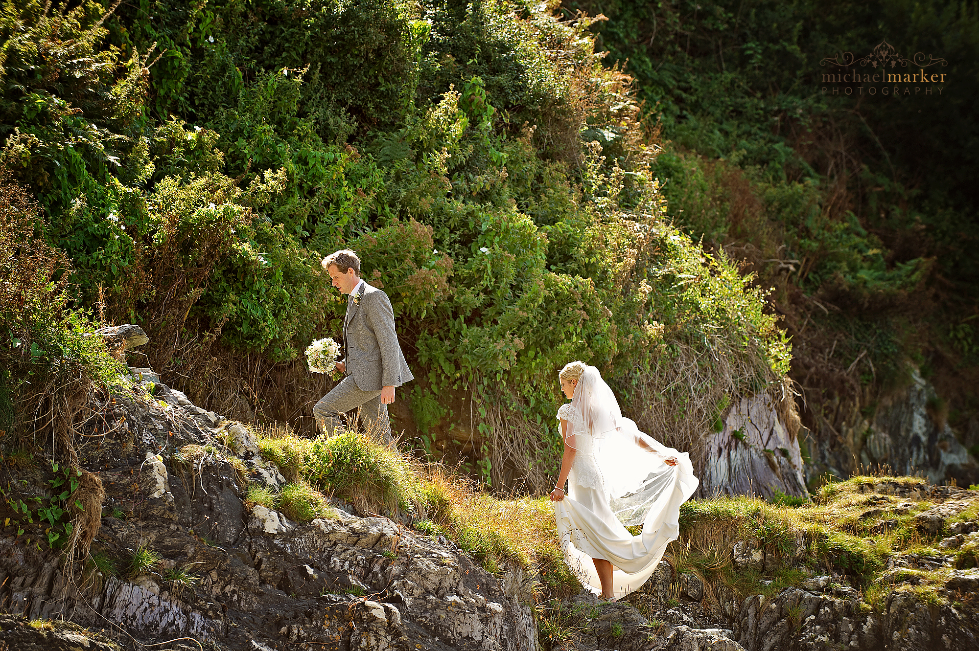 Bride and groom walking up a cliff path from the beach at Polhawn Fort