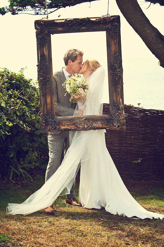Bride and groom kissing in DIY phtobooth frame hanging from a tree at Polhawn