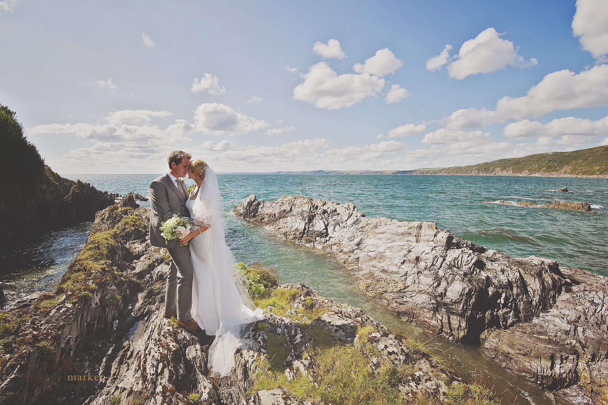 Bride and groom kissing on Polhawn Fort's private beach