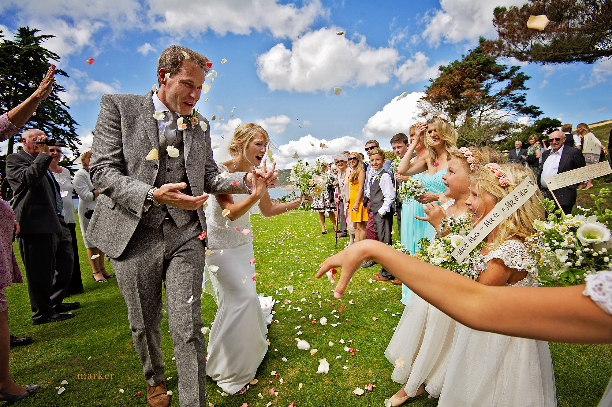 Bride and groom aon lawns of Polhawn Fort encouraging flower girls to through more confetti