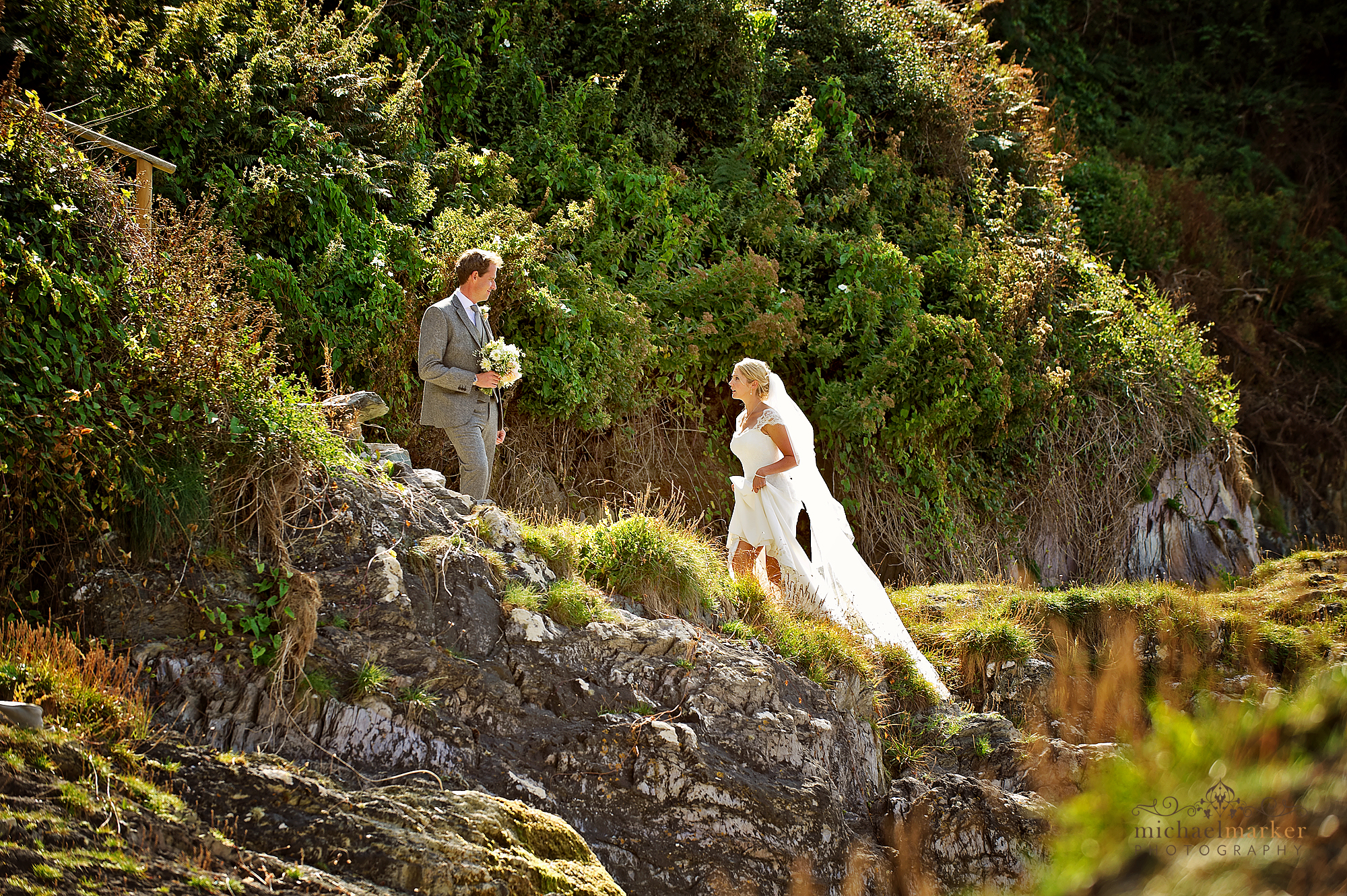 Bride and groom looking at each other as they walking up from the beach at Polhawn Fort