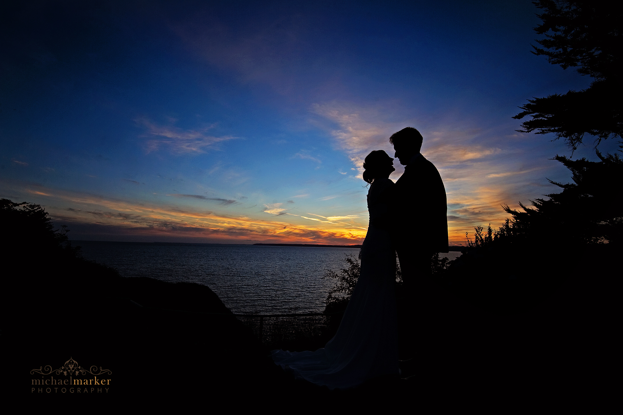 Bride and groom sunset silhouette embracing at Polhawn Fort