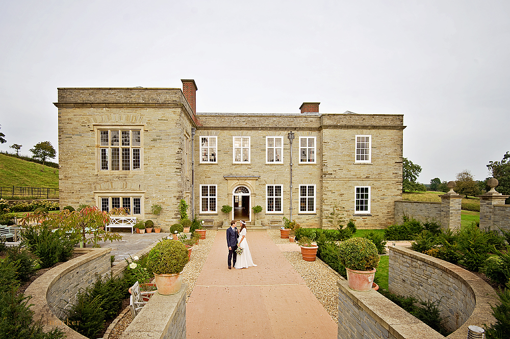 Bride and groom in front of Shilstone House on their wedding day