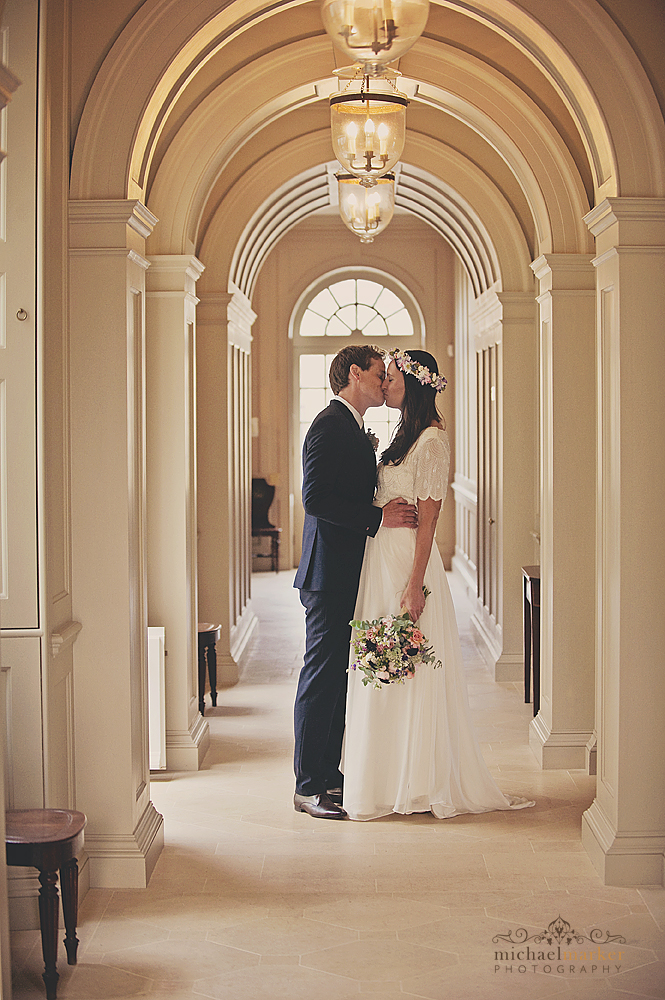 Bride and groom kissing in the hallway of Shilstone House in Devon