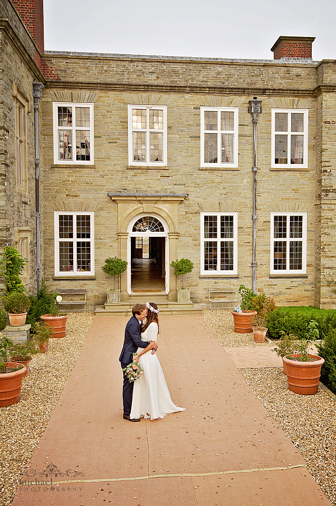 Bride and groom kissing in front of Shilstone House