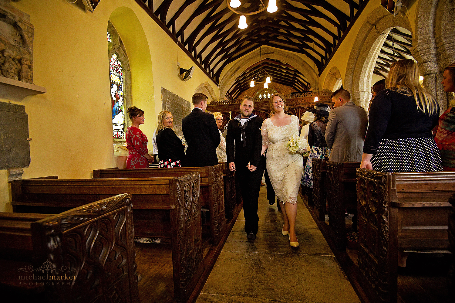 Bride and groom walking p the aisle at Sheepstor Church in devon