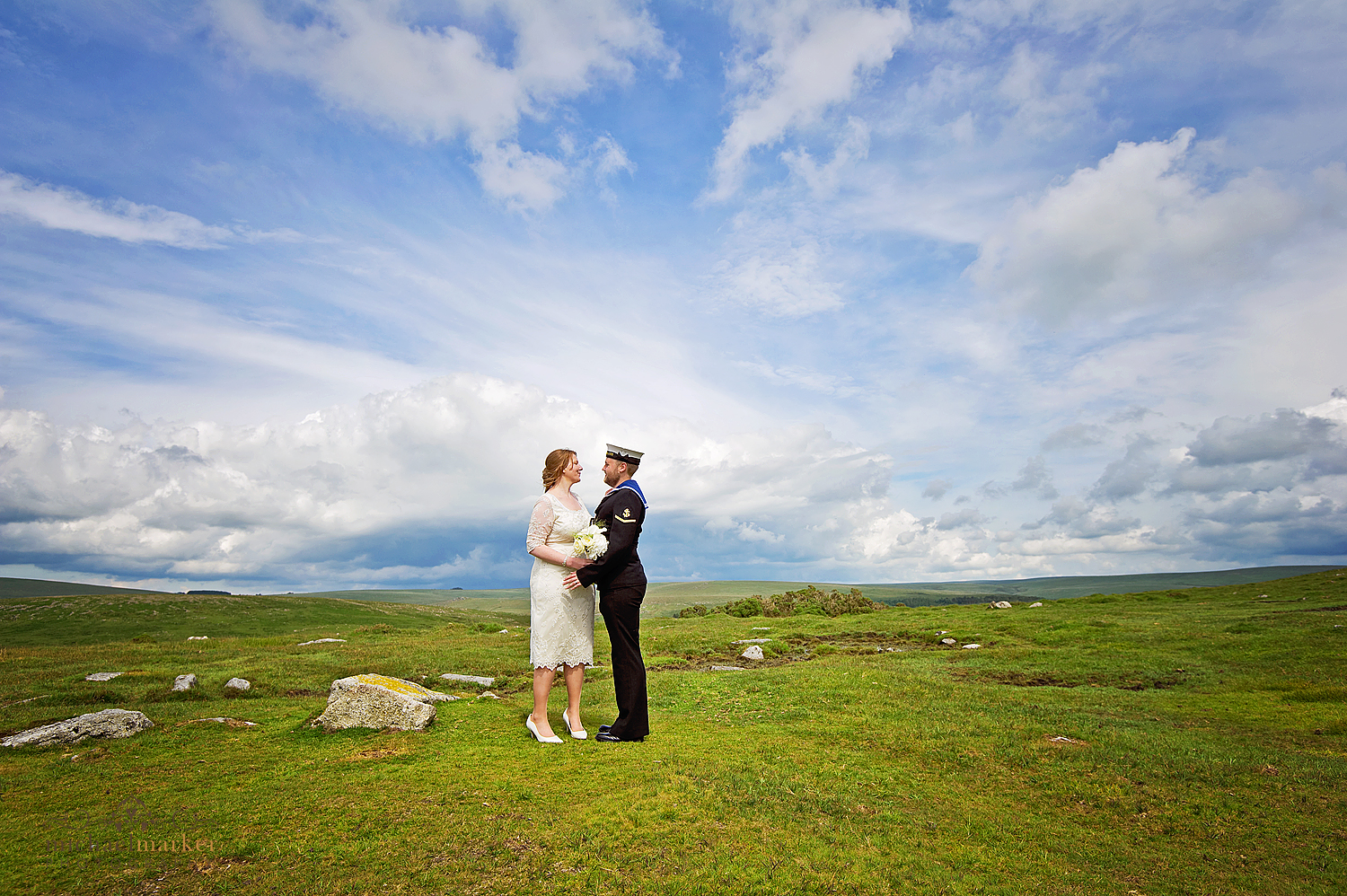 Bride andf groom looking at each other overlooking Dartmoor in devon