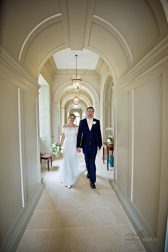 Bride and groom walking the hallway at Shilstone House in Devon