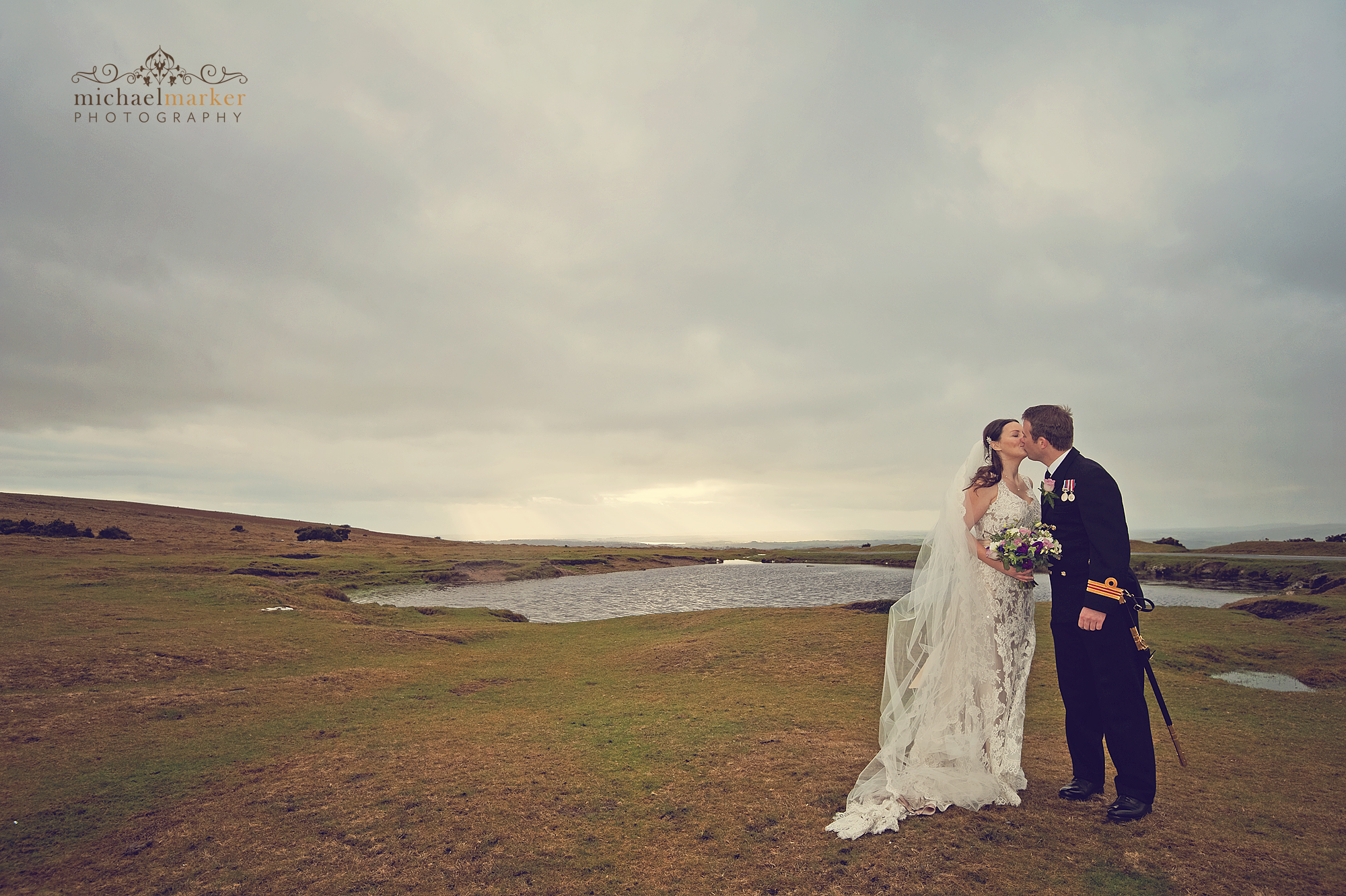 Wedding day couple kissing on Dartmoor with view of Plymouth behind