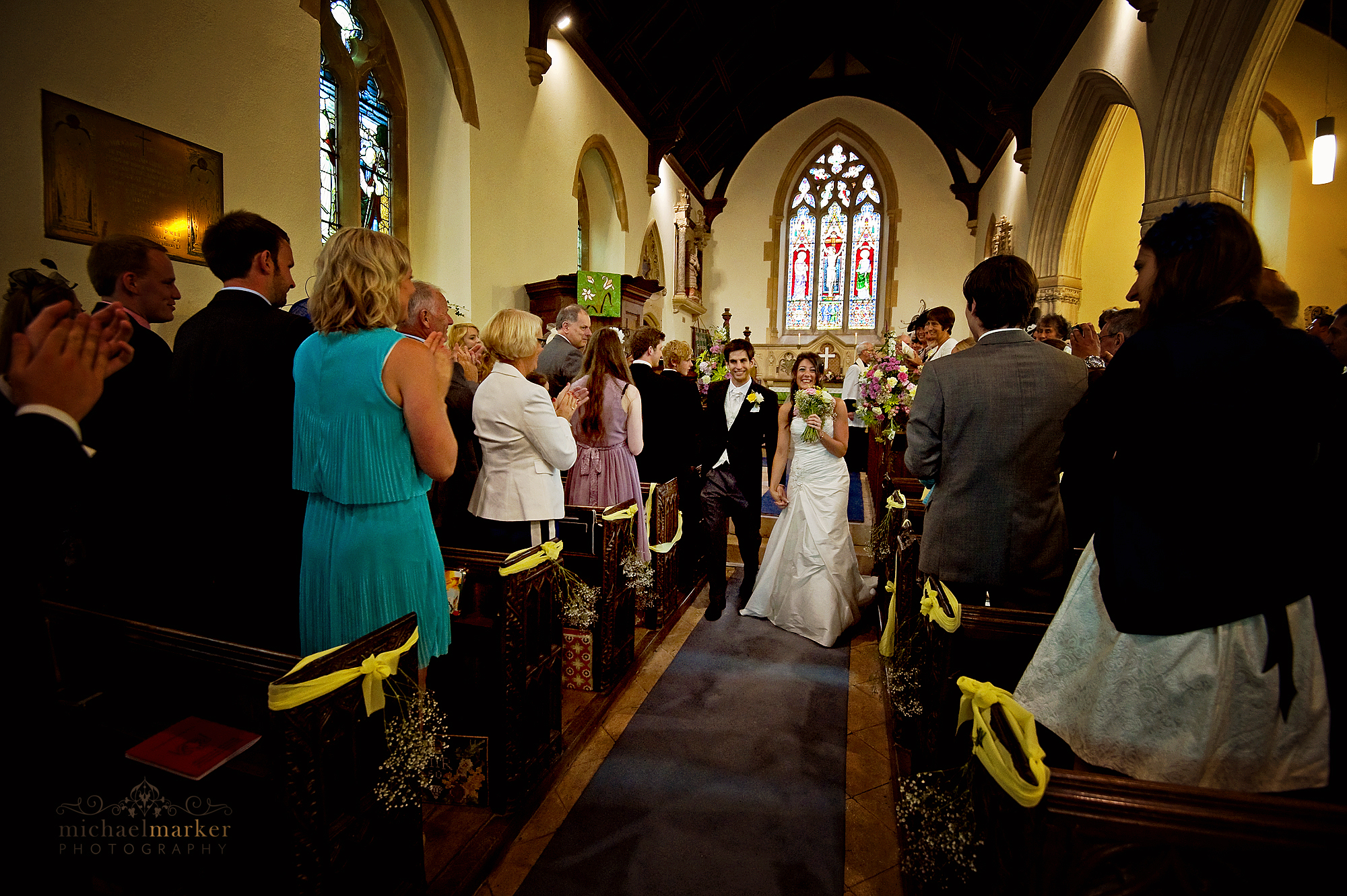 Bride and groom walking down the aisle of Bickleigh Church in Devon